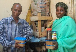 Jamila and her husband display their peanut butter. Business skills training has empowered many woman caregivers to engage in effective business practices. Photo Credit: Fernando Maldonado, USAID/MARKETS