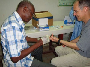 (At left) Mr. Moussa Diagne, Entomologist with the Parasite Control Service in Senegal, performs a Rapid Diagnostic Test (RDT) for malaria on Dr. Zeke Emanuel, Special Advisor on Health Policy to the Director of the White House Office of Management and Budget