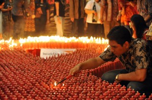 Indonesian volunteers light candles during a ceremony to mark World AIDS Day in Jakarta. Photo Credit: Adek Berry/AFP