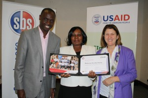 Kenyatta National Hospital Chief Nurse Philomena Maina (center) receives her LeHHO certificate from Strathmore Business School Dean Edward Mungai (left) and Academic Director Joan Mansour of MSH (right). Photo Credit: MSH