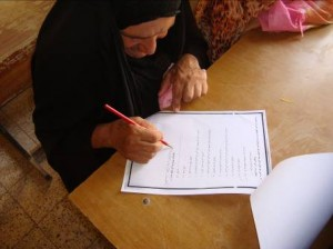 Elderly student takes her final literacy exam to qualify for graduation. Photo Credit: Mercy Corps