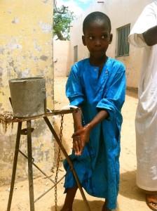 A child washing their hands in Senegal. Photo Credit: Ryan Cherlin/USAID