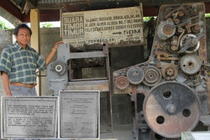 This Timor-Leste printing press was destroyed in 1999 during violence following a referendum on independence. Today, the artifact remains near the current press at Suara Timor Lorosae – the first independent newspaper in Timor-Leste – to remind people of the importance of a free and independent media. Salvador J. Ximenes Soares, shown here beside the press, is the newspaper's editor. USAID funded the destroyed press and the one that replaced it.   Photo credit: Mauricio Borges, USAID