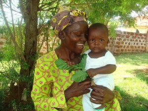 "Esther Ouma with her son, Barrack, in the Busia district of western Kenya. After losing her first two babies, Ouma successfully delivered Barrack after a visit from a community health worker who provided a link to health services and support groups available to expectant mothers in some Kenyan communities. ""I will forever be grateful,"" says Ouma, who attributes her good health and that of her child to the health worker's intervention. Photo credit: Bibianne Situma, AMREF"