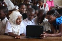 Children around a laptop in school. Photo Credit: USAID