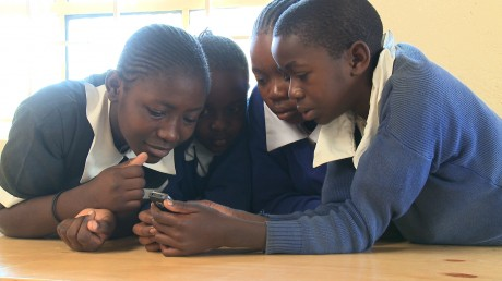 Children play the Half the Sky mobile games in Kenya. Photo credit: Ed Owles, Worldview