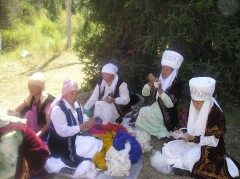 Svetkul Akmatova (center, in the traditional blue Kyrgyz jacket) and members of her organization, Altyn Kol Women's Handicraft Cooperative, busily prepare wool for their handmade carpets. Photo Credit: B. Jakypova, American Council for International Education