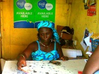 A woman sells prepaid mobile phone airtime credits. Photo Credit: Devex.