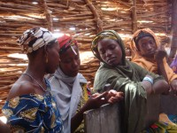 A group of women composes a text message in rural Niger. Photo Credit: Joshua Haynes