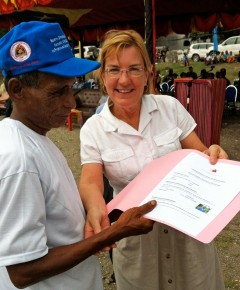 Ambassador Fergin hands out a claims certificate at a ceremony in Liquica, Timor-Leste. Photo Credit: Tetra Tech.