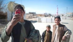 An Afghan youth uses his mobile phone to take pictures in Musa Qala. Photo credit: Dmitry Kostyukov, AFP