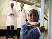 A child peers around the corner in the waiting room of the HIV Comprehensive Care Clinic of Meru District Hospital in Kenya's Eastern province as two pediatricians stand in the background. Photo credit: Mia Collis, Elizabeth Glaser Pediatric AIDS Foundation
