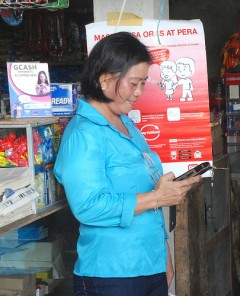 Mobile banking saves women time and money.  With mobile services, women no longer have to make all-day treks to and from the bank. Photo credit: USAID
