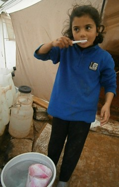 Using clean water from her family's new  bucket, Haneen* brushes her teeth with the  toothbrush received from a USAID partner in  Olive Grove Camp (Photo: USAID Partner)  *Name changed to protect identity Improving Hygiene for Displaced Syrians