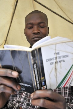 A young man reads the Kenyan Constitution. Photo Credit: Photo credit: USAID/Riccardo Gangale