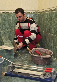 Shalva Grigalashvili, one of USAID/NEO beneficiaries, tiling a guesthouse bathroom in Kvishkheti village of Khashuri municipality. Photo credit: USAID/NEO