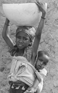 Nine year old girl with a brother or sister on her back and about 25 pounds of water on her head. She just walked 3.2 miles one way to fetch this dirty water. She does this three times ad day — everyday. Niger, 2006. Photo Credit: Gil Garcetti