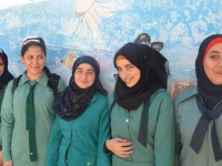 Girls in Jerash pose in front of their school's storage tank that is painted to look like an aquarium. Photo credit: Alysia Mueller