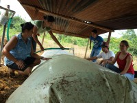 USAID and community members take care of an EARTH biodigester. Photo credit: USAID