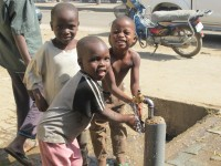 Three young boys look to be having some fun while they use a public standpipe in Bauchi town, Nigeria. This is one of the sites where town residents retrieve water since few have water taps at their homes. In December 2011, USAID's Sustainable Water and Sanitation in Africa project signed an agreement with town officials to help them expand and improve services to residents. Demand for water in urban areas like Bauchi exceeds 200,000 cubic meters per day—nearly four times the volume the town's water utility is currently able to pump to its customers. Photo credit: Emily Mutai, SUWASA