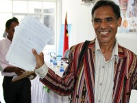 """Parliamentarian Mateus de Jesus (CNRT) shows notes received from constituents during the """"Listen to the People's Voice"""" forum in Maliana, Timor-Leste, in April 2013. Photo credit: Paul Randolph, USAID"""