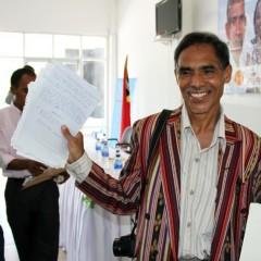 "Parliamentarian Mateus de Jesus (CNRT) shows notes received from constituents during the ""Listen to the People's Voice"" forum in Maliana, Timor-Leste, in April 2013. Photo credit: Paul Randolph, USAID"