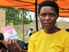 Scovia Ketusiime holds a Healthy Baby voucher. Photo credit: SHOPS