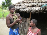 A health worker refers to her mobile phone for information while making a house visit. Photo credit: World Vision