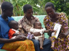 Beatrice, holding Gabriel, and Grace, with baby Mary, listen as CHW Jane Akoth (right)  counsels them on their health choices. Photo Credit: USAID