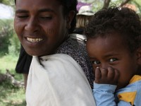 A mother plays with her infant as she waits outside a health post in Ethiopia. Photo credit: USAID