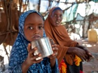Three-year-old Maryan drinks milk. Her mother Habiba (left) enrolled her in Save the Children's milk voucher program when she showed signs of malnutrition. Photo credit: Susan Warner. February 2013