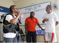 Ruy Pinto, a representative from the Coral Triangle Support Partnership, shows fisherman Feliz Fernandes how to use dive equipment during a community meeting in Manatuto. Photo credit: Cristovão Guterres, USAID/Timor-Leste