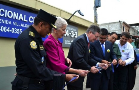USAID-Guatemala Director, Kevin Kelly (center), cuts the symbolic ribbon at the official reopening of the Villalobos II police substation in Villanueva, Guatemala. From left, National Civilian Police (PNC) Director, Telémaco Pérez; Police Reform Commissioner, Adela de Torrebiarte; USAID's Kevin Kelly; BANTRAB President, Sergio Hernández; Minister of Government, Mauricio López Bonilla; and Villanueva Mayor, Edwin Escobar. Photo credit: USAID
