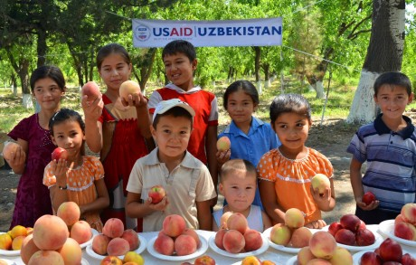 Rural children enjoy prize-winning fruits of the Ferghana Valley at a USAID-sponsored agricultural contest. Photo Credit: U.S. Embassy in Tashkent, Uzbekistan