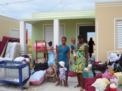 A beneficiary prepares to move her belongings into her new USAID-funded house near Cabaret, Haiti, in September 2013. Photo credit: USAID