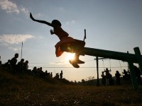 In Swaziland, just before sunset, a young girl tests out a new seesaw on a playground built by the Elizabeth Glaser Pediatric AIDS Foundation at the Mkhulamini Clinic. Photo credit: Jon Hrusa, Elizabeth Glaser Pediatric AIDS Foundation