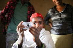 A young married girl is learning how to use a camera during the first day of a week long Participatory Research Activity using the  Photovoice method. She, along with nine other program participants were asked to use photography to document their lives and the impact the TESFA program had on them. Photo credit: Robin Hayes