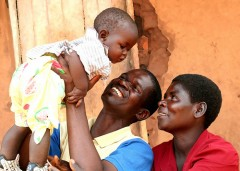 A family celebrates with their child, a sign of togetherness and healthy living. Photo credit: USAID/B. Deutsch