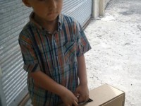A young Syrian boy receives a box of clothing at a USAID-supported distribution site. Photo credit: USAID Partner