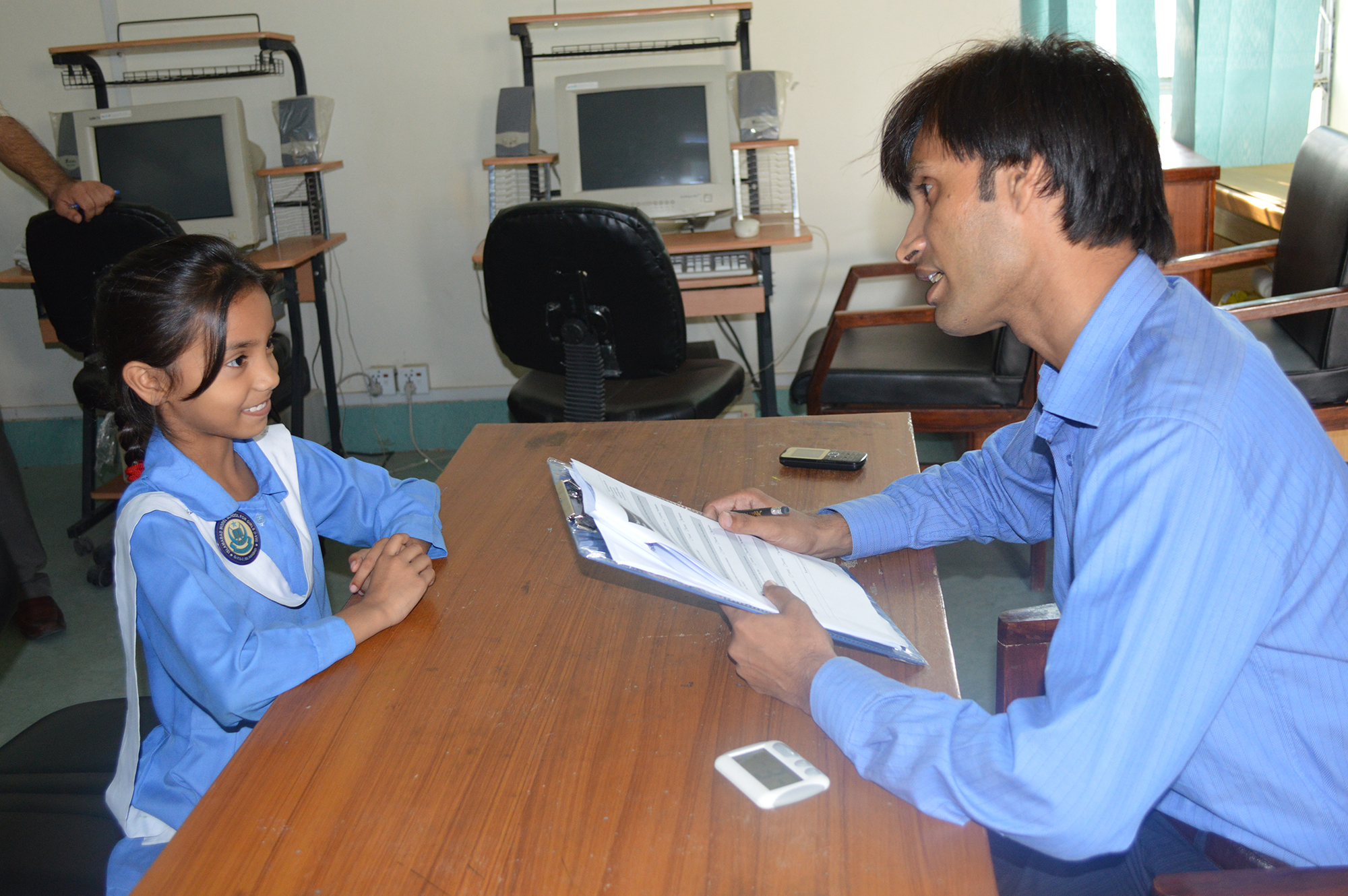 The evaluator in a primary school in Pakistan talks with the young girl about the reading assessment, explaining how it works and what she will be doing.