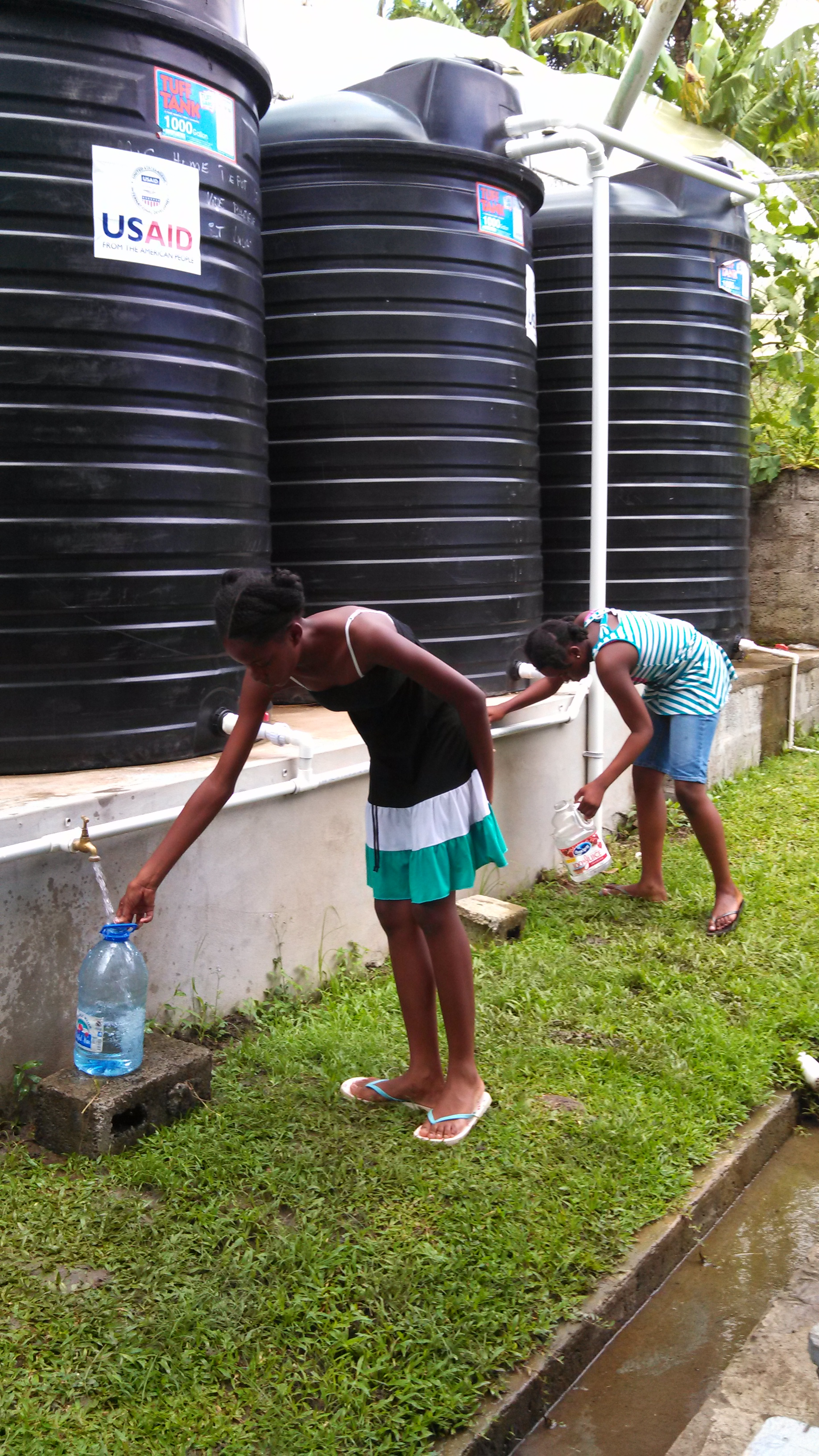 Girls in Laborie use water from storage tanks after a December 2013 storm disrupted regular water service. Photo courtesy of the Laborie Disaster Preparedness Committee.