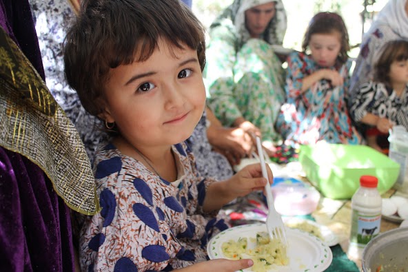 "A little girl in Tajikistan eats mashed potatoes with greens, which her mother prepared for her. Over 5,000 Tajik children under 5 years old tasted new foods such as pancakes (""blini"") with cottage cheese and vegetable salads that their mothers prepared for them after a training. / USAID"