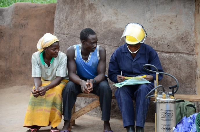 A couple in Ghana sits with an insecticide spray technician. / Erin Schiavone, Abt Associates