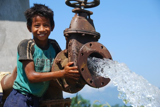 Here a Nepalese boy demonstrates the water flow of a USAID-built electric tube well used for irrigation in the Terai region of Nepal. Patrick D Smith/USAID