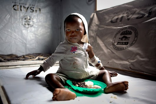 USAID and the Medical Relief International Charity (Merlin) support cholera treatment centers in Goma, Democratic Republic of Congo.  Pictured is a young child suffering from cholera and receiving food aid from the Agency.  /  Frederic Courbet