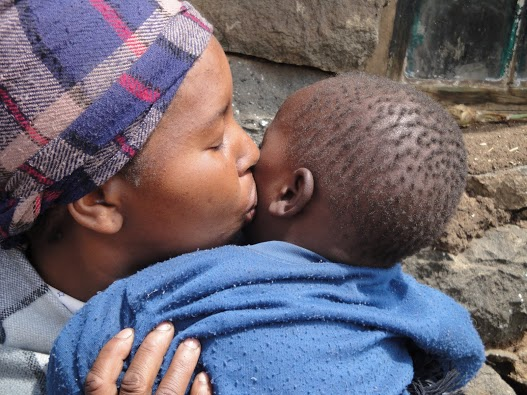 "This photo took third place in the FrontLines photo contest. Maamohelang  Hlaha tenderly kisses her young son Rebone. An HIV-positive mother of four, Hlaha's  village is inaccessible by vehicles and a three-hour hike from the nearest health clinic.  She receives HIV treatment through the Riders for Health program, which is funded  by USAID and run by the Elizabeth Glaser Pediatric AIDS Foundation. As part of the  program, pony riders and motorcycle riders transport blood tests, drugs and supplies to  Lesotho's remote mountain health clinics. The system allows people to receive HIV test  results sooner, access life-saving drugs and ensure an uninterrupted supply of medication.  Rebone, whose name means ""we have witnessed,"" was born HIV-free in August 2008. / Reverie Zurba, USAID/South Africa"