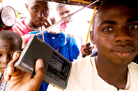 A minicab driver listens to a radio broadcast in a market in Abeche, Chad (2009). / Internews
