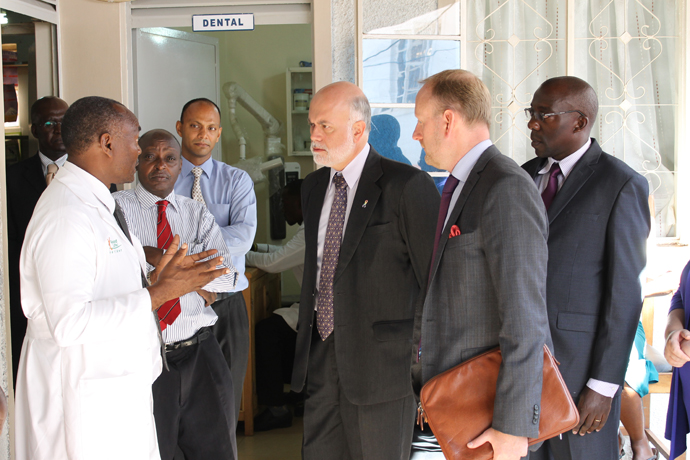 Dr. Bemera explains Amb. DeLisi, Amb. Andersson and the rest of the team about how he used the loan to scale up activities at his clinic.