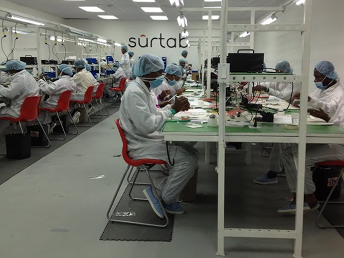 Workers at Haiti's Surtab factory carefully assembly tablets.