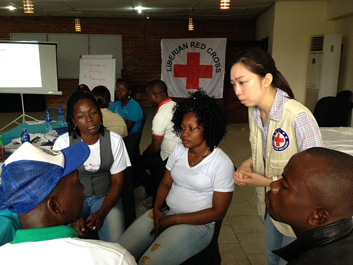 Eliza Yee-lai Cheung (right) a clinical psychologist with the International Federation of the Red Cross, listens as counselors in Monrovia share stories about helping families cope with Ebola